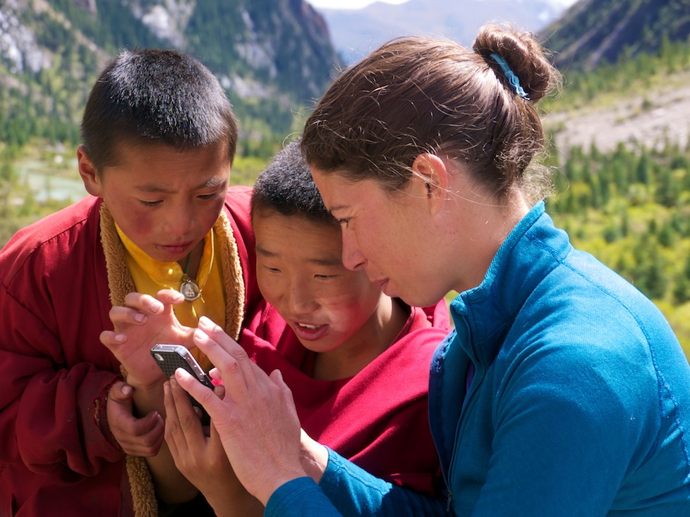 Annie Wilson sharing iPhone photos with young monks, Genyen Massif, Sichuan China